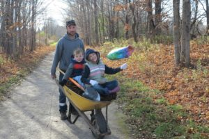 Man with two kids in wheelbarrow doing volunteer work